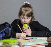 Girl doing homework and eating apple, green apple and schoolgirl doing homework royalty free stock images
