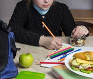 Girl doing homework and eating dried fruits royalty free stock image