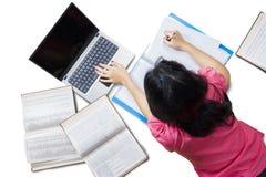 Girl doing homework on the floor Stock Images