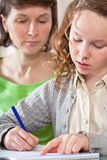 Girl doing homework with her mom Royalty Free Stock Image