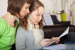 Girl doing homework with her mom Stock Images
