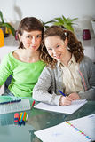 Girl doing homework with her mom Royalty Free Stock Photos