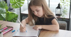 Girl doing homework at home. Cute little girl doing homework in her book at home stock video footage