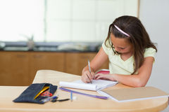 Girl doing homework in the kitchen Stock Images