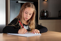 Girl doing homework. In the kitchen Royalty Free Stock Image