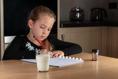 Girl doing homework. In the kitchen with a glass of milk Stock Photos