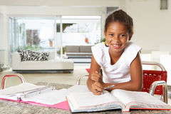 Girl Doing Homework In Kitchen Stock Image