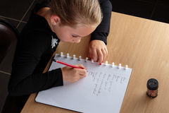 Girl doing homework in the kitchen Royalty Free Stock Photos