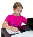 Girl doing homework for a laptop. Isolated on white Royalty Free Stock Photo