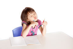 Girl doing homework, looking at her pencils Stock Photography