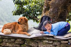 Girl doing homework outdoor. A girl doing homework in a nepalese village Annapurna Circuit, Nepal Royalty Free Stock Image