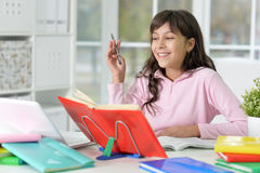 Girl doing homework. Portrait of a girl doing homework, reading book Stock Images