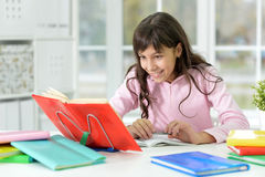 Girl doing homework. Portrait of a girl doing homework, reading book Stock Photos