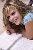 Girl doing homework and smiling. A girl smiling while she is doing her homework Stock Photo