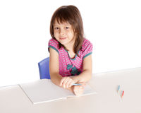 Girl doing homework smiling at camera Stock Photo