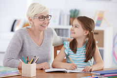Girl doing homework with tutor. Happy girl doing homework with private tutor Stock Photo