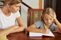 Girl doing homework under control on mother royalty free stock photo