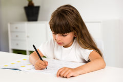Girl doing homework. Young caucasian girl doing her homework while sitting at table Royalty Free Stock Photography