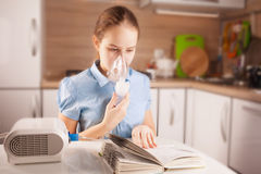 Girl doing inhalation and reading book Royalty Free Stock Photography