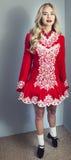 Girl doing Irish dance in red. Beautiful blond girl doing Irish dance in red and white costume Royalty Free Stock Image