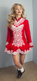 Girl doing Irish dance in red. Beautiful blond girl doing Irish dance in red and white costume Stock Photo