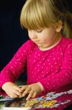Girl doing jigsaw puzzle Stock Photography