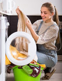 Girl doing laundry at home Stock Photos