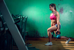Girl doing lunge exercise. Young adult caucasian girl doing lunge exercise indoor with kettlebell Royalty Free Stock Image