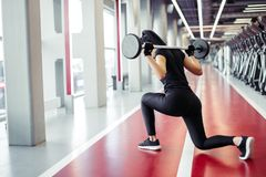 Girl doing lunges with barbell in modern gym Royalty Free Stock Photos