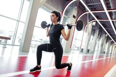 Girl doing lunges with barbell in modern gym. Woman performing lunges with barbell at gym stock photography