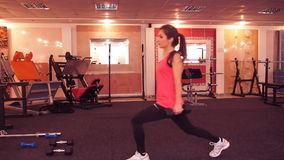 Girl doing lunges with dumbbells. She crouches alternately on one leg at the gym stock video footage
