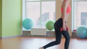 Girl doing lunges with dumbbells in a gym