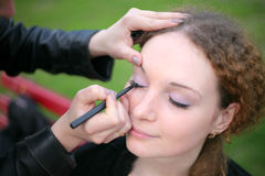 A girl doing make-up. Girl doing makeup in the park before shooting Stock Images