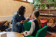 Girl doing make up in cafe stock photography