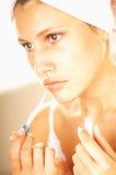 Girl doing makeup Stock Images