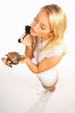 Girl doing makeup. Blonde Girl doing makeup close up isolated on white bacground royalty free stock photo