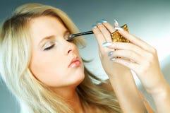 Girl doing makeup Stock Photos
