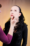 Girl doing makeup. With eyes looking up royalty free stock image