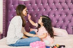 Girl Doing Makeup Of Beautiful Mother In Bedroom stock images