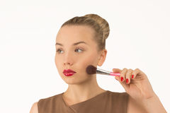 Girl doing makeup with brush. On a white background Stock Photos