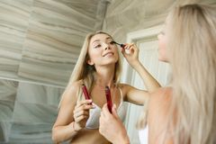 Girl doing makeup in front of a mirror in the bathroom. stock photo