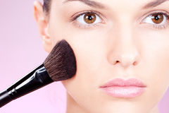 Girl doing makeup with powder brush. Young woman doing makeup with powder brush royalty free stock image