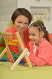 Girl doing math exercises with  mother. Little girl doing math exercises with her mother at home Stock Photos