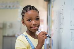 Girl doing math at whiteboard. African student girl doing math problems on white board. Portrait of black schoolgirl doing math addition at whiteboard in Royalty Free Stock Images