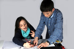 Girl doing maths homework. Teenager girl sitting at her desk  doing her maths school  homework, she gets help from her brother Stock Photography