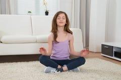 Girl Doing Meditation. Girl In Sportswear Doing Meditation In Living Room Stock Photo