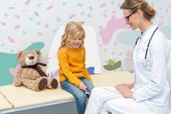 Girl doing neurology examination for doctor. Beautiful little girl doing neurology examination for doctor with knee jerk hammer stock photo