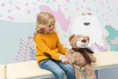 Girl doing neurology examination of teddy bear. Adorable little girl doing neurology examination of teddy bear while sitting on sofa royalty free stock images
