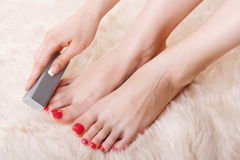 Girl doing pedicure Stock Photography