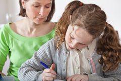 Girl doing prework with her mom Royalty Free Stock Image